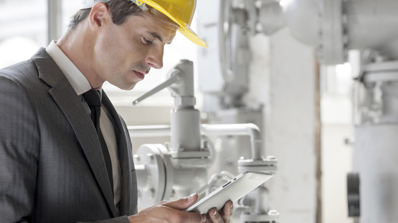 engineer with mobile device, plant interior, pipes, tablet
